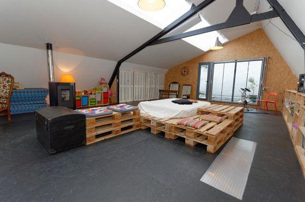 Lit fabriqué avec du bois de palette dans un grand loft