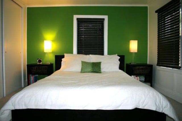 chambre avec mur vert et meubles noirs