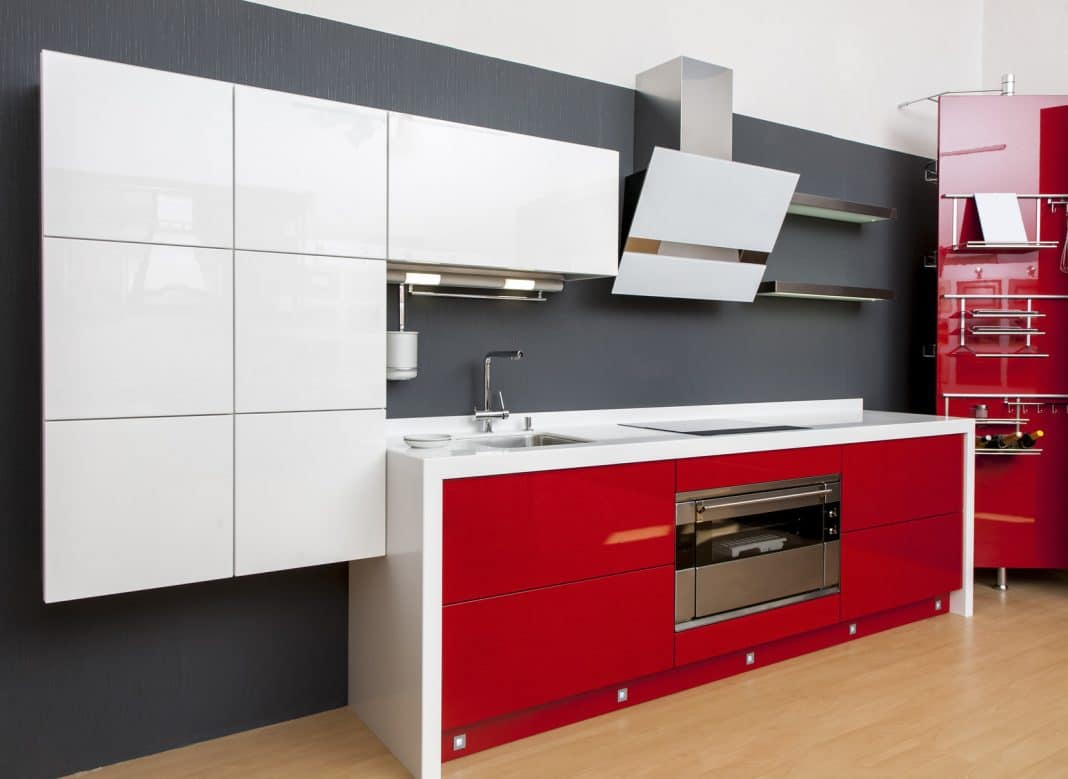 Un joli mur gris ardoise et des placards blanc et une cuisine rouge