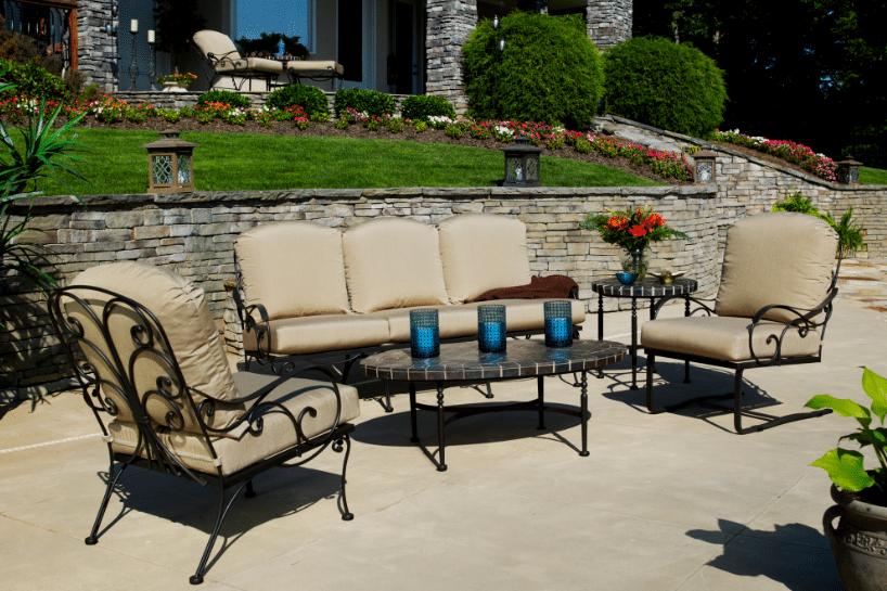 Salon de jardin en fer forgé avec coussins en tissu beige. Volutes en fer forgé plein haut de gamme.